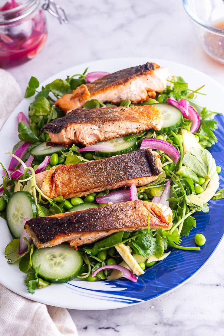 Salmon salad on a blue and white platter on a marble background