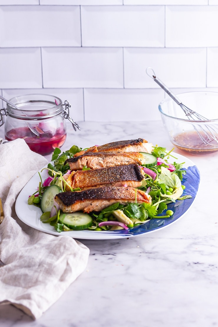 Side on shot of salmon salad on a blue platter with dressing in the background