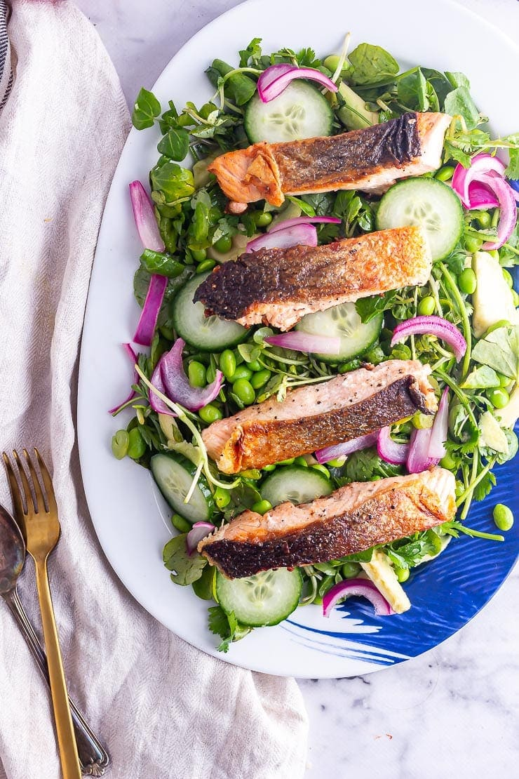 Salmon fillets on a salad with watercress and cucumber