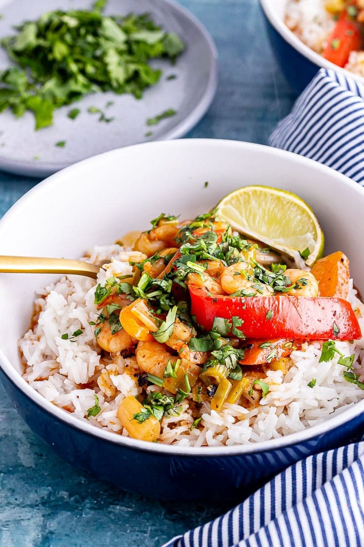 Close up of Thai prawn curry in a bowl with a gold fork