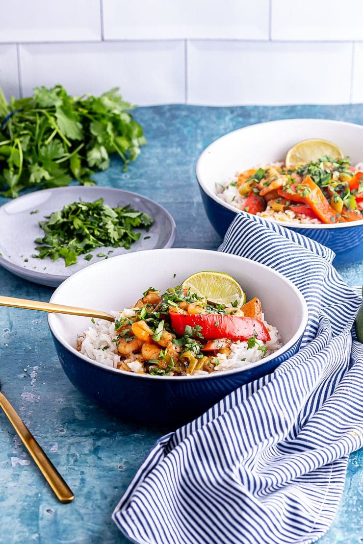 Side on shot of Thai prawn curry in blue bowls with a gold fork on a blue surface