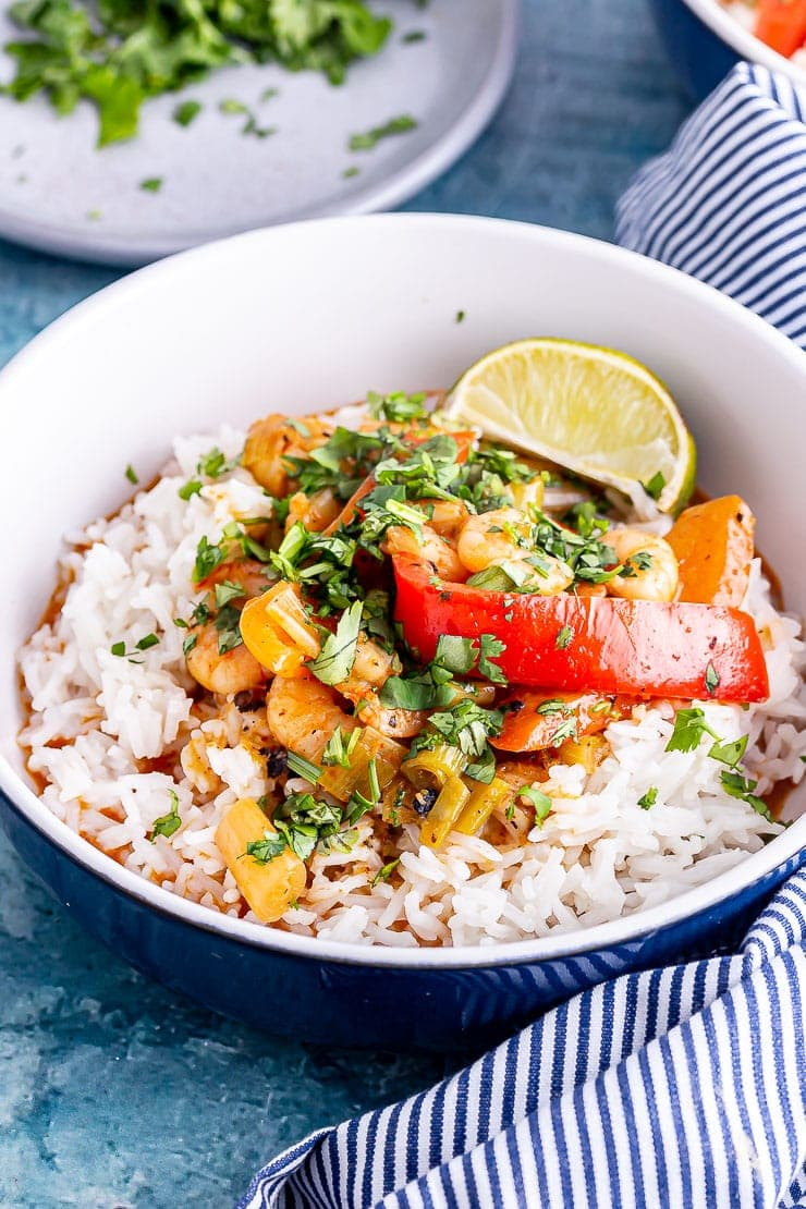 Blue bowl of prawn curry with rice and a striped cloth