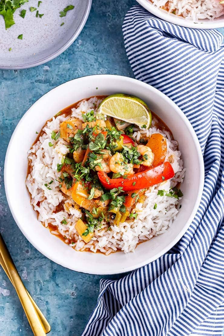 Overhead close up of Thai prawn curry with a striped cloth on a blue background