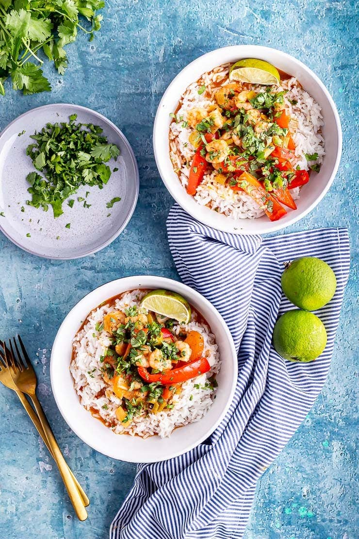 Overhead shot of two bowls of Thai prawn curry with limes and herbs on a blue background