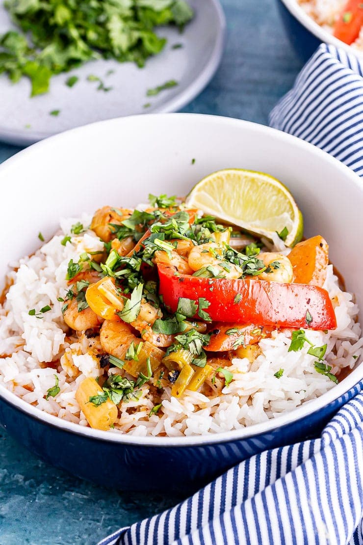 Blue bowl of Thai prawn curry with rice and lime