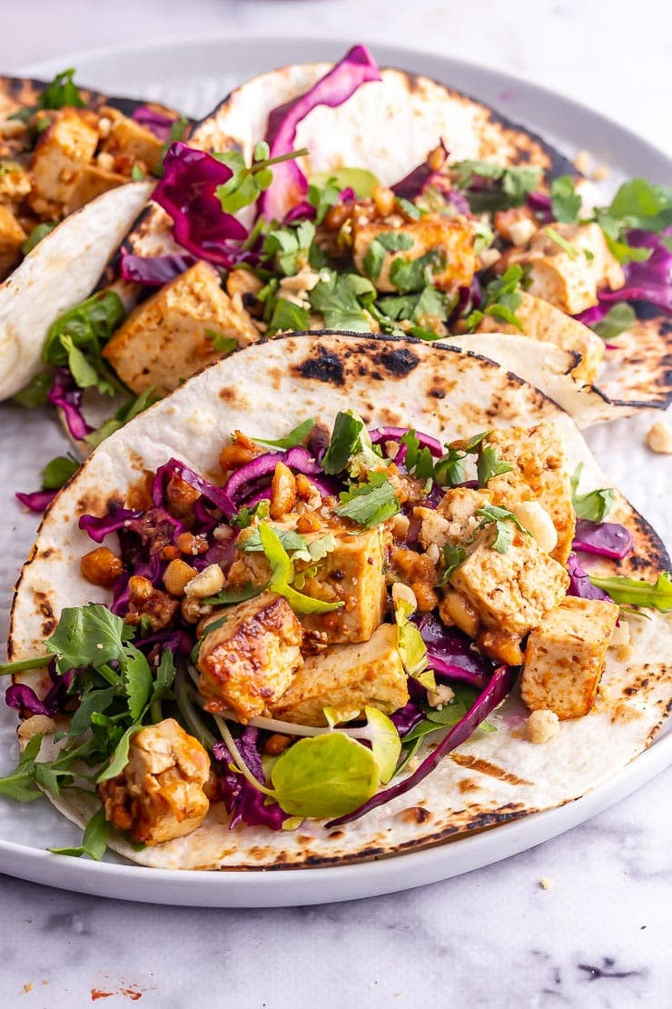 Peanut tofu tacos with cabbage slaw and coriander on a grey platter