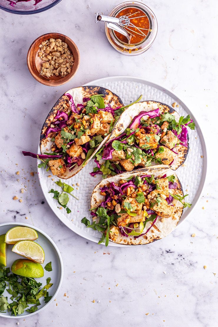 Plate of tacos with a plate of lime wedges, chopped peanuts and peanut sauce on a marble background