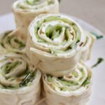 Cucumber sandwich rolls on a white plate