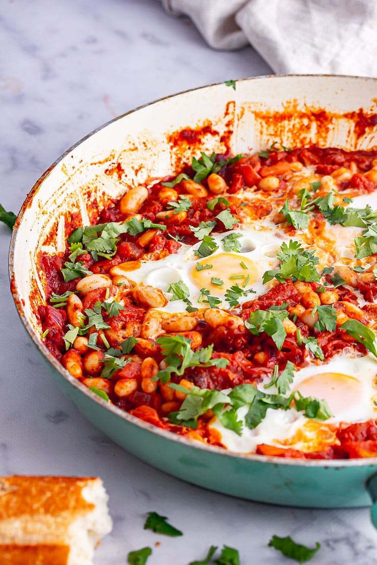 Side on shot of spicy bean skillet with eggs with herbs and bread