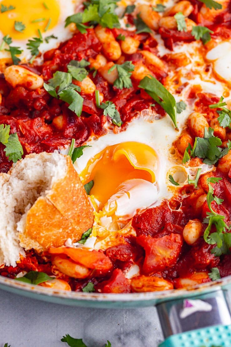 Egg broken with bread in spicy beans in a blue skillet