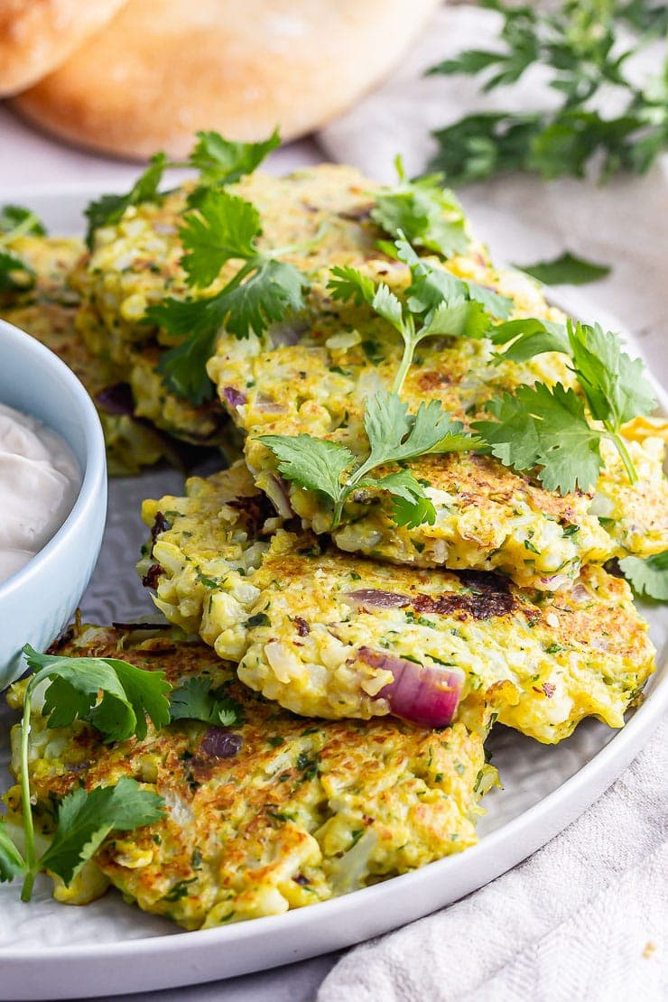 Close up of cauliflower fritters with herbs on a grey plate
