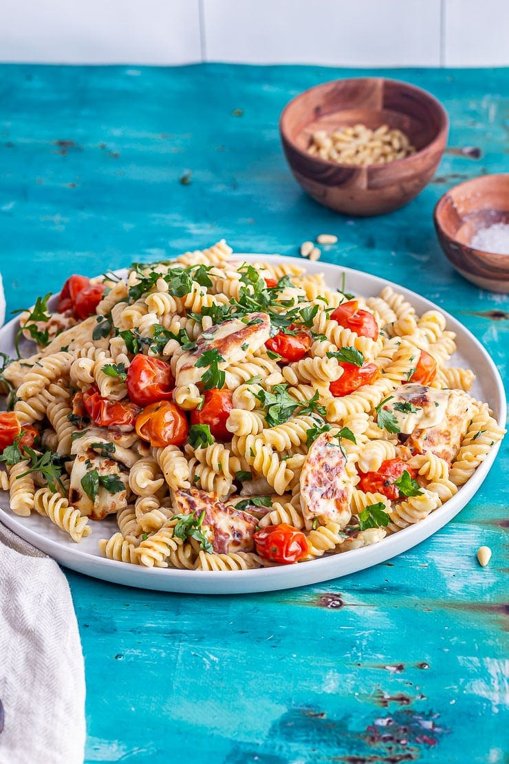 Platter of halloumi pasta with tomatoes on a bright blue background