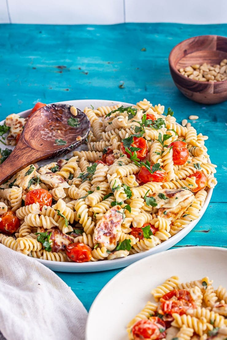 Wooden spoon with halloumi pasta in front of a wooden bowl of pine nuts