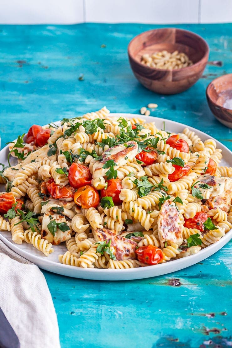 Halloumi pasta with tomato and parsley on a blue background