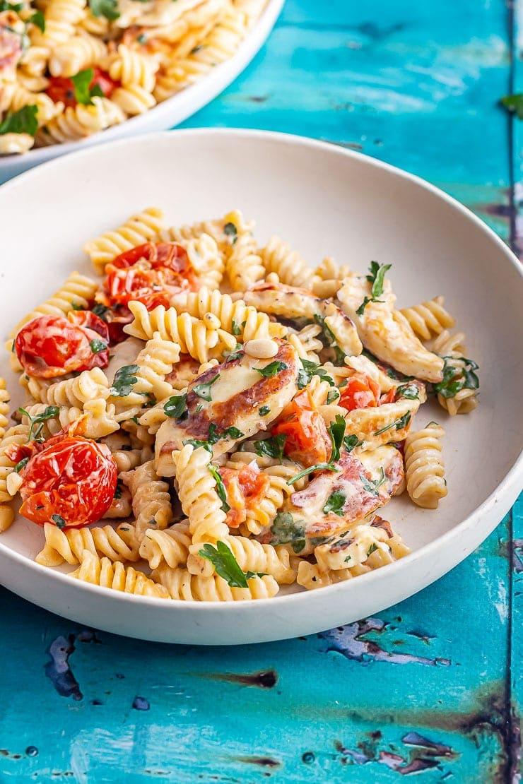 Cream bowl of halloumi pasta on a blue background