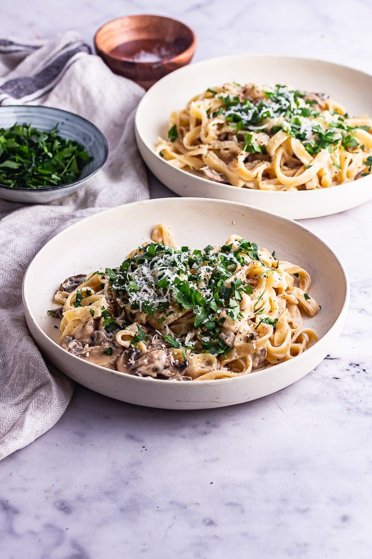 Two bowls of mushroom tagliatelle with parsley on a marble background