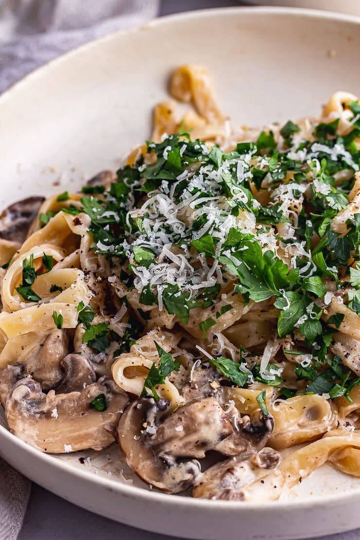 Close up of mushroom tagliatelle with parsley in a cream bowl