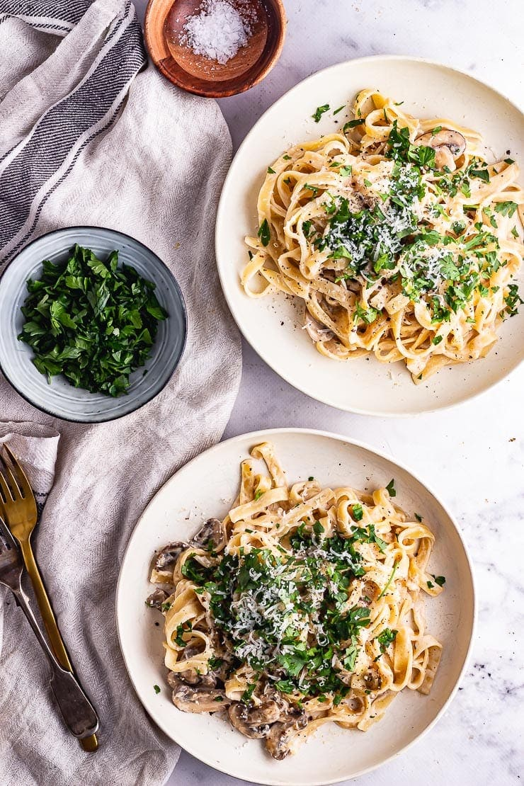 Overhead shot of mushroom tagliatelle in white bowls on a marble surface