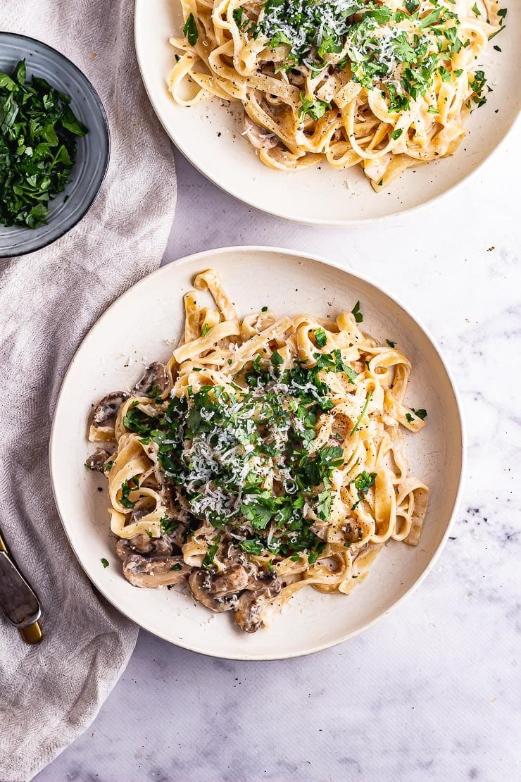 Overhead shot of mushroom tagliatelle with herbs on a marble surface
