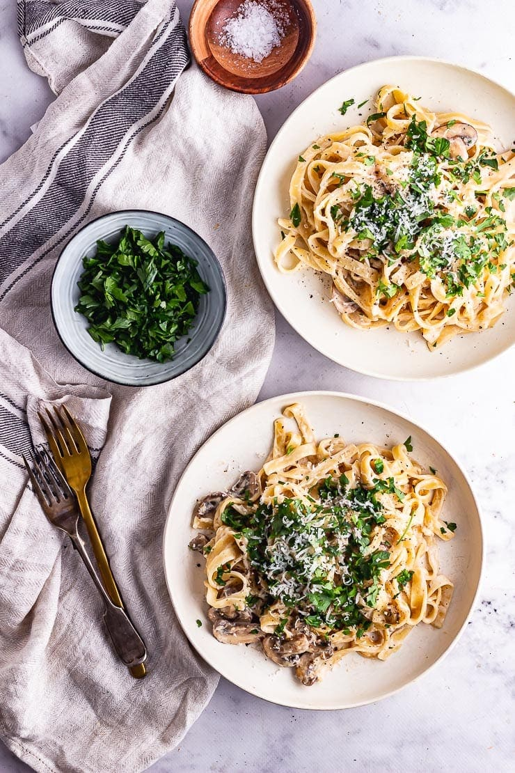 Overhead shot of two bowls of mushroom tagliatelle with parsley and forks