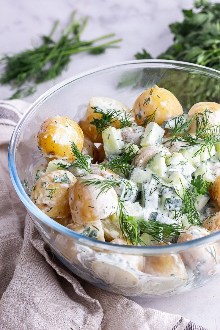 Close up of a glass bowl of healthy potato salad with a cream cloth