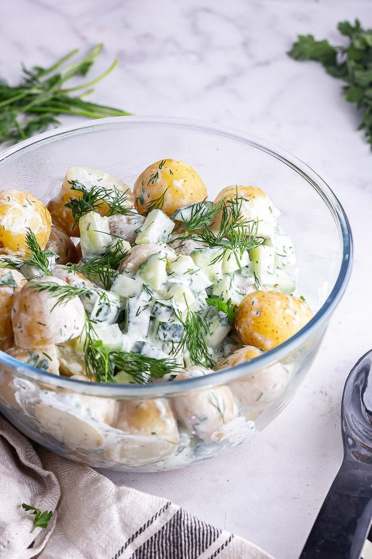 Side angle shot of healthy potato salad on a marble surface