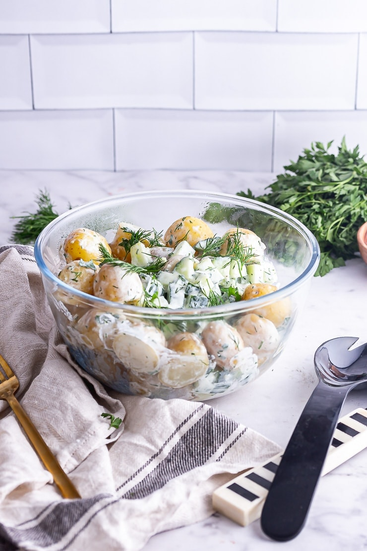 Side on shot of healthy potato salad in front of a white brick wall with herbs in the background