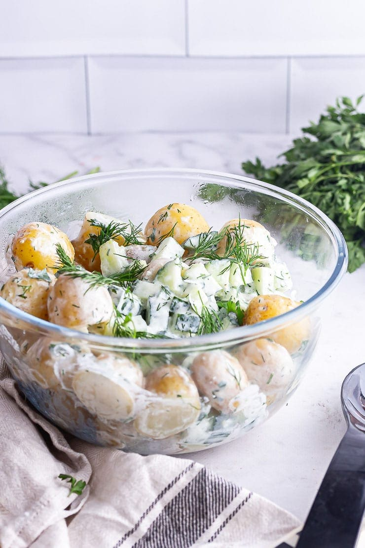 Glass bowl of potato salad with herbs on a marble surface