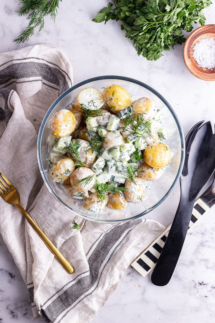 Overhead shot of healthy potato salad with herbs, salt and salad servers