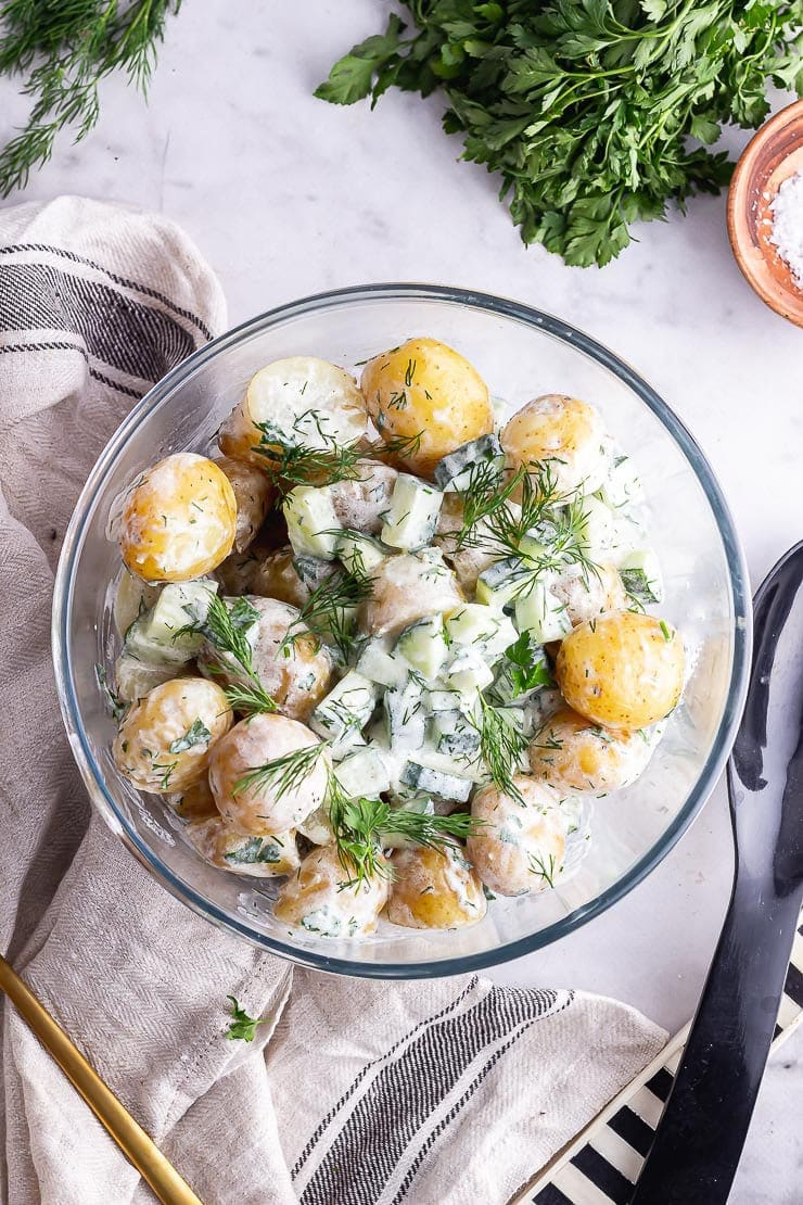 Overhead shot of healthy potato salad on a marble background with salt and herbs