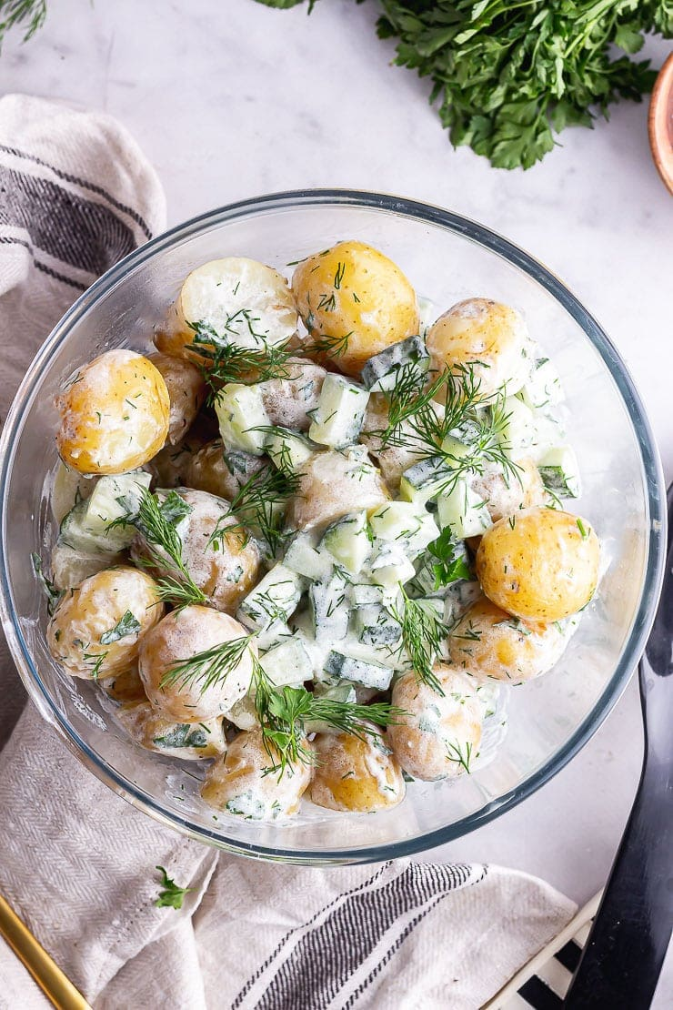 Overhead shot of healthy potato salad with herbs on a marble background