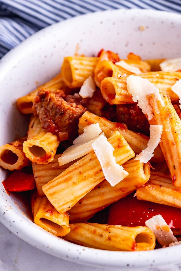 Close up of sausage pasta with parmesan in a white bowl