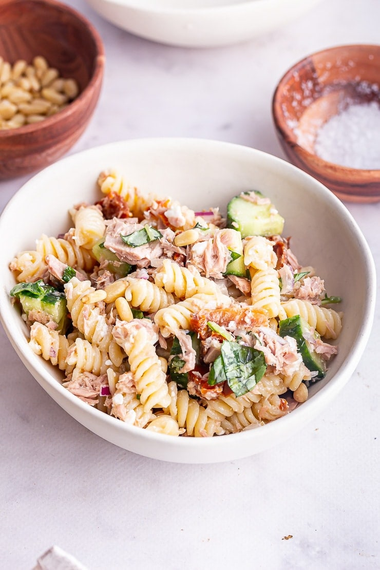 Side angle shot of tuna pasta salad in a white bowl on a marble surface