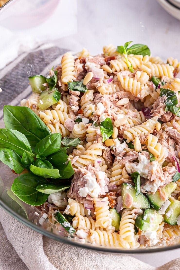 Tuna pasta salad in a glass bowl with basil