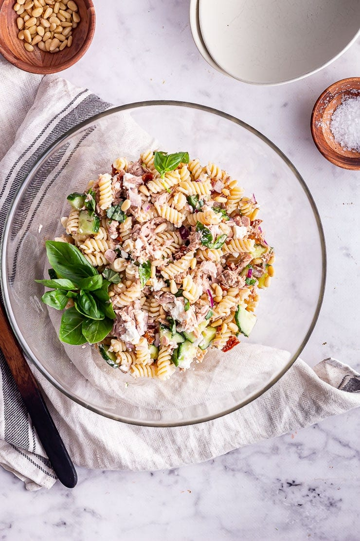 Overhead shot of tuna pasta salad in a glass bowl with salt and pine nuts