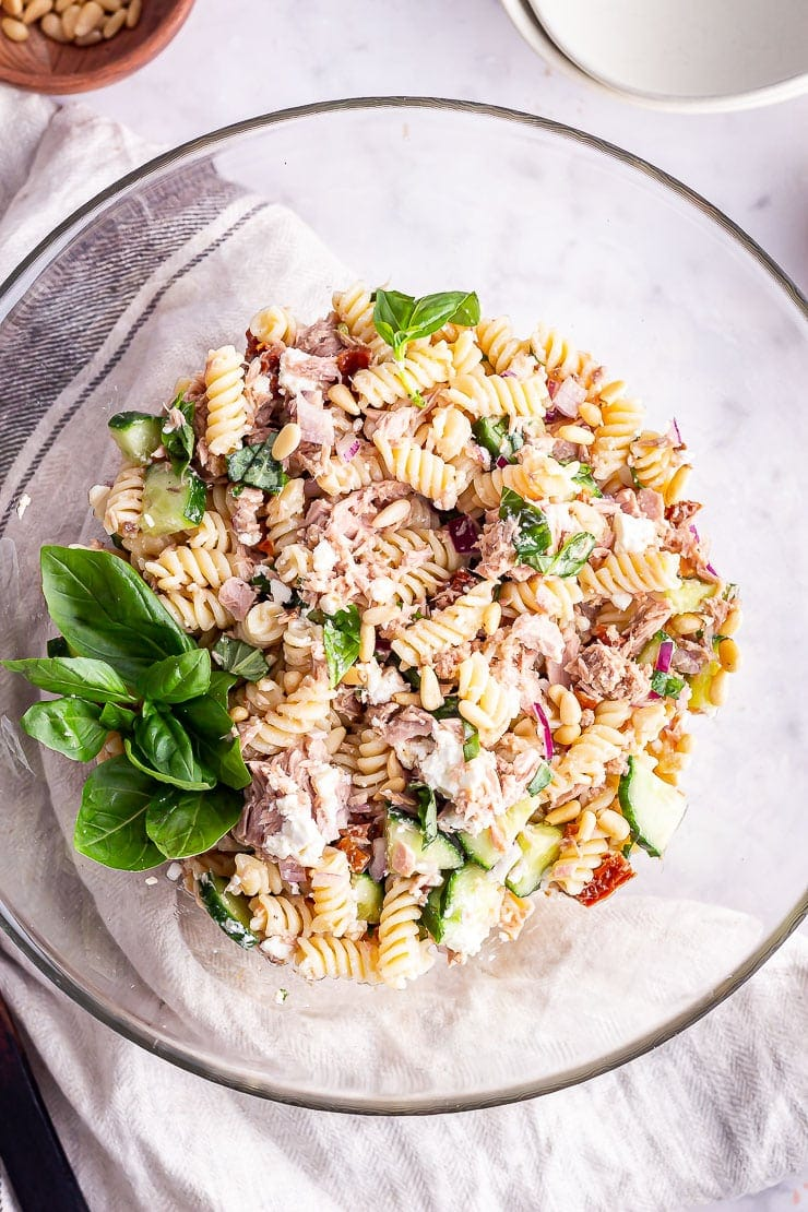 Overhead shot of tuna pasta salad in a glass bowl with basil