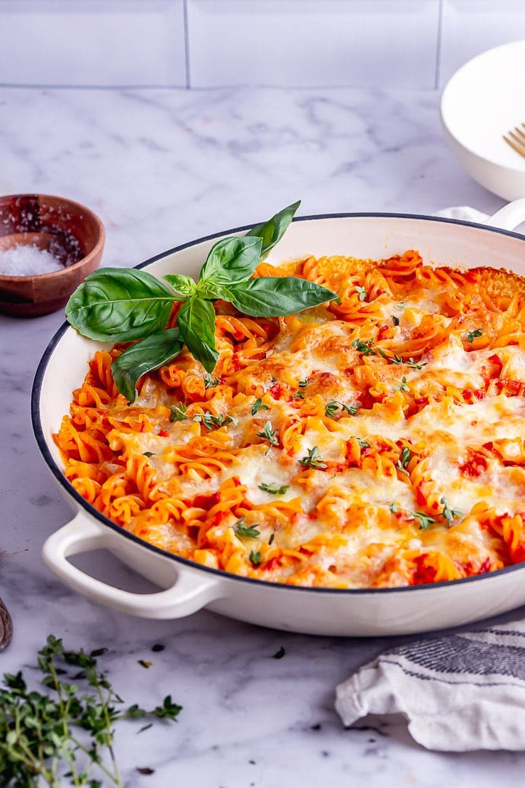 White dish of cheesy pasta bake with red pepper sauce on a marble background