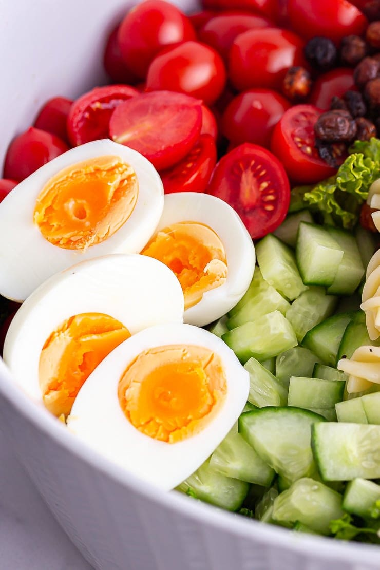 Close up of hard boiled eggs in a salad with cucumber and tomato