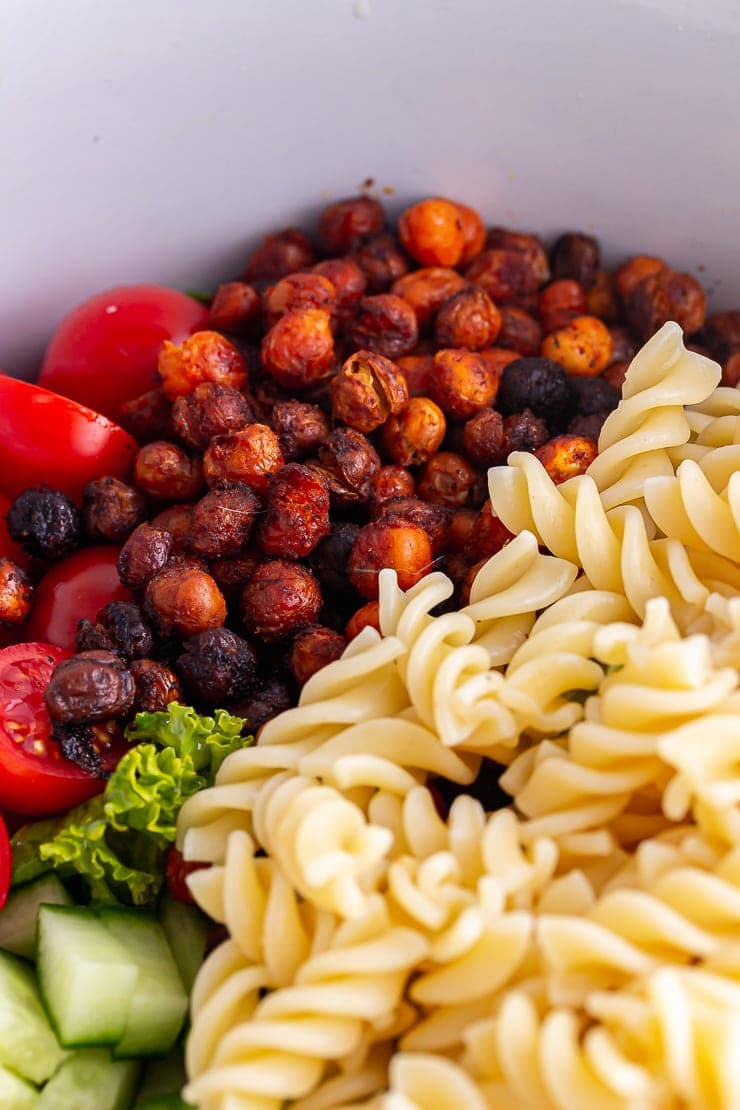 Close up of roasted chickpeas and pasta in a salad