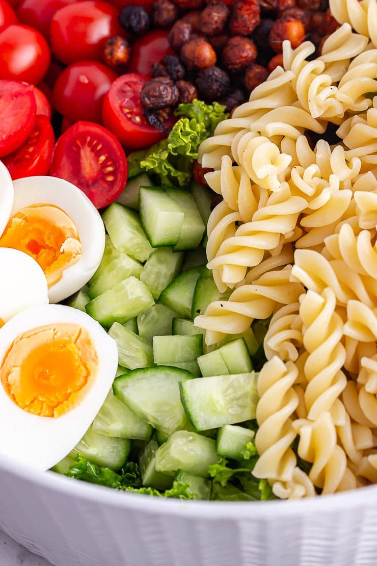 Close up of pasta, cucumber and eggs in a cobb salad