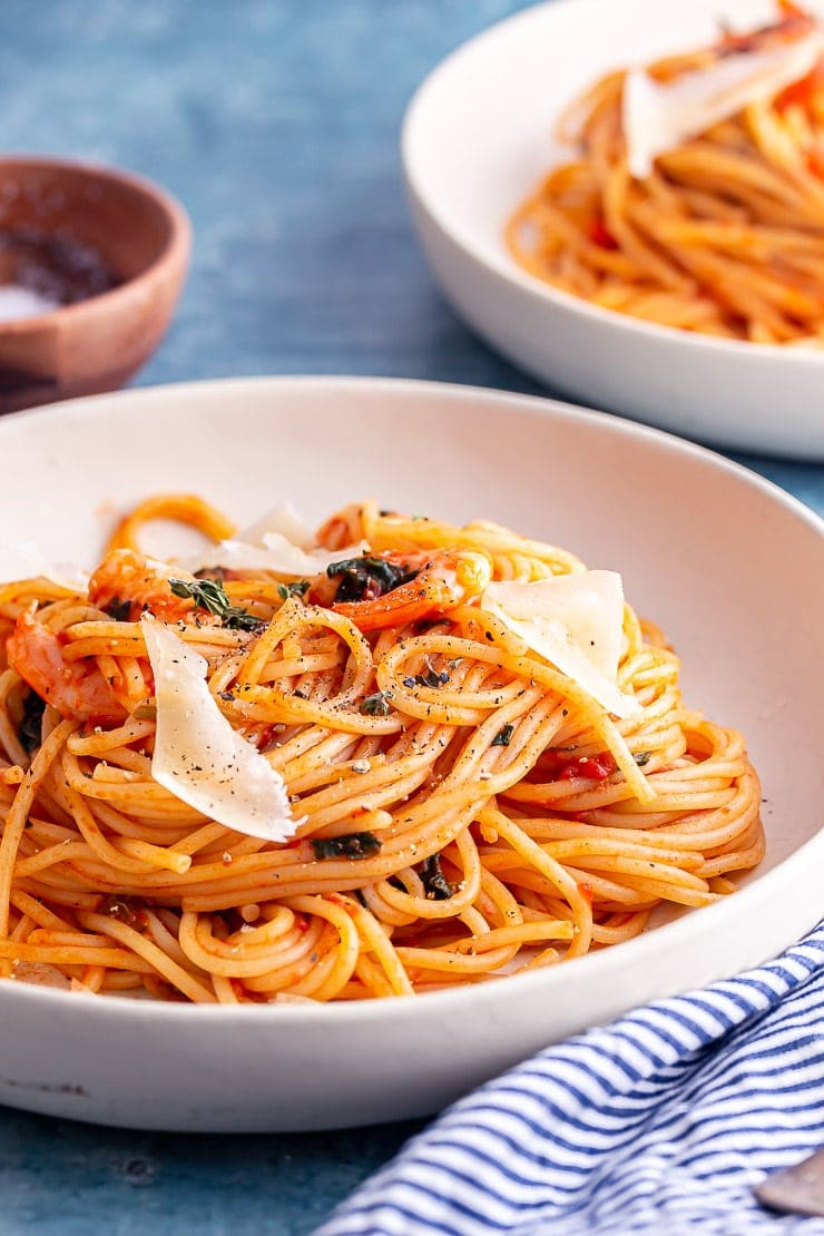 Close up of prawn spaghetti with parmesan in a white bowl with a striped cloth