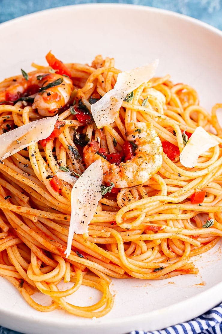 Close up of prawn spaghetti with parmesan in a white bowl