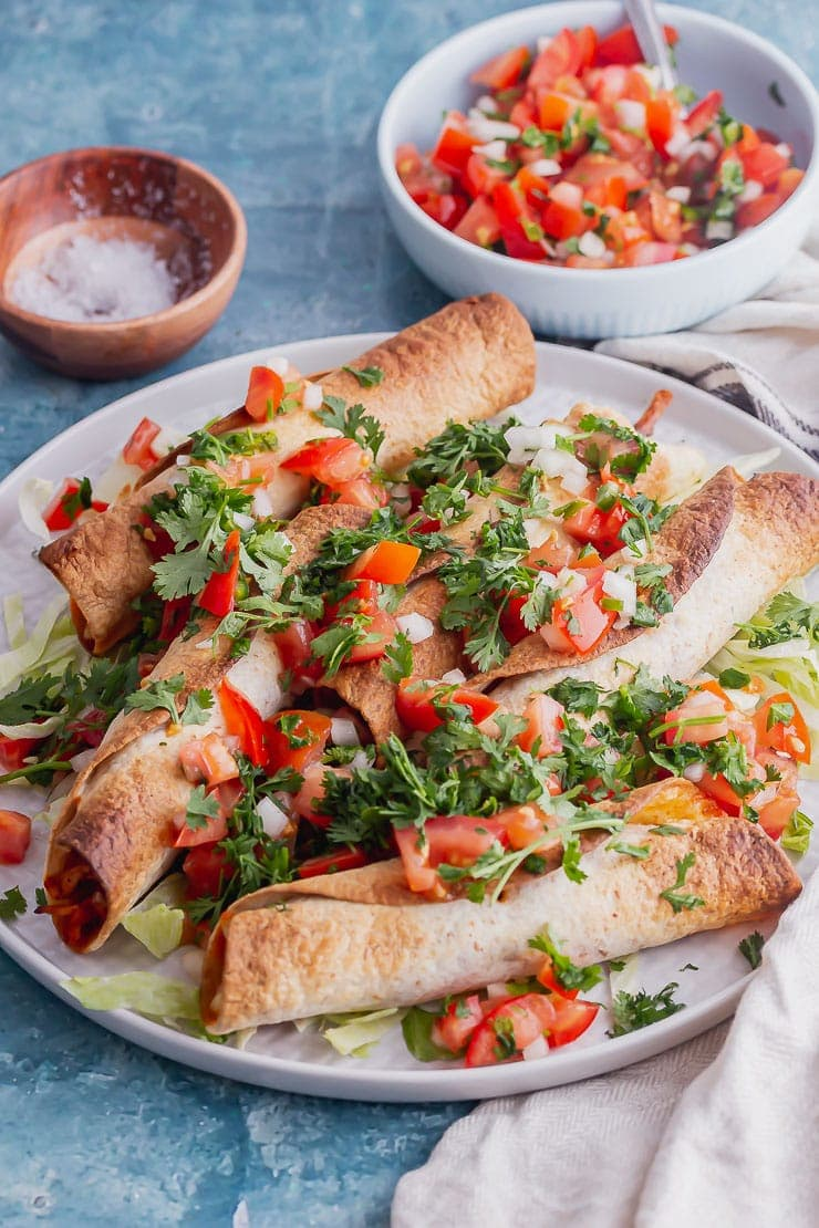 Side on shot of grey plate of taquitos with chicken and pico de gallo