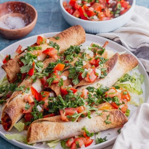 Grey plate of chicken taquitos with salsa on a blue background