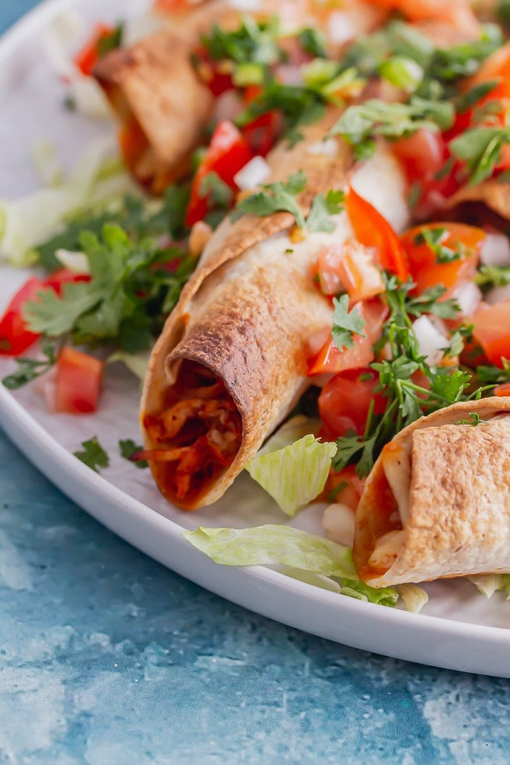 Close up of chicken taquitos with lettuce and tomato on a blue background