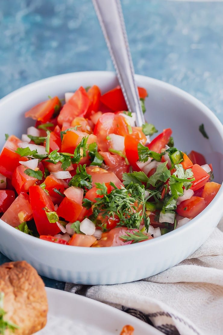 Close up of pico de gallo in a blue bowl with a spoon