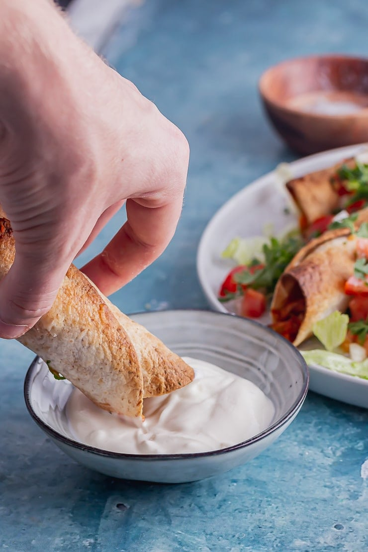 Chicken taquito being dipped in sour cream in a blue bowl