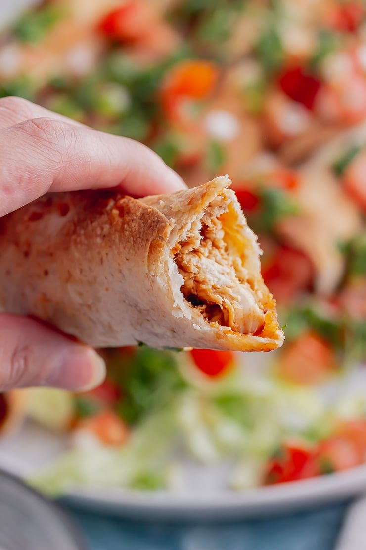 Close up of a chicken taquito with a bite taken