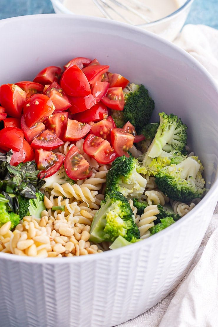 Tomatoes and broccoli with pasta in a grey bowl