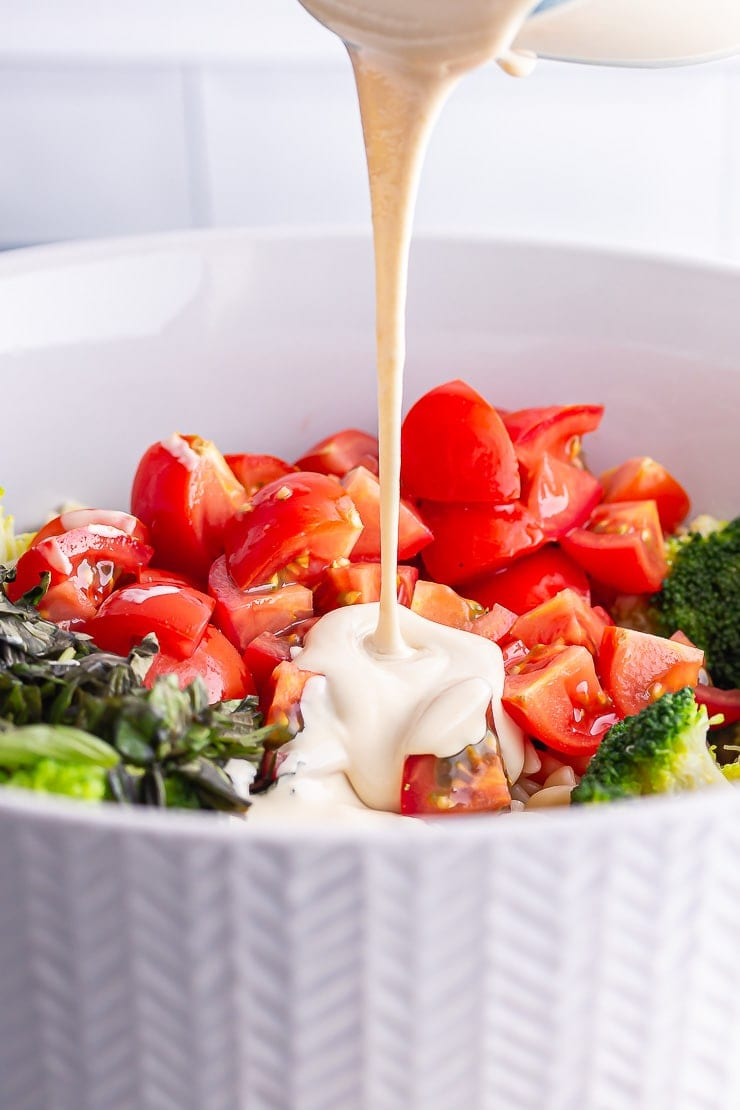 Dressing pouring into a vegan pasta salad with tomatoes and broccoli